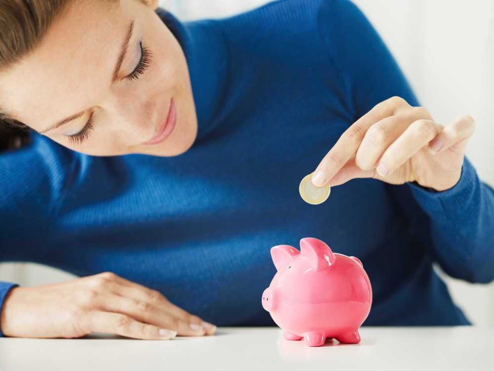 Woman saving money in piggy bank