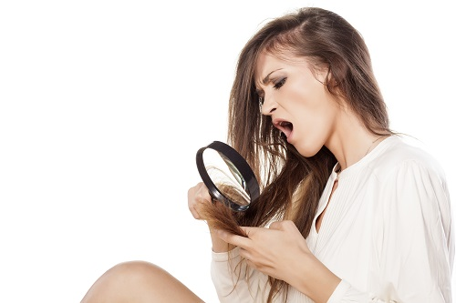 woman looking through a magnifying glass ends of her hair